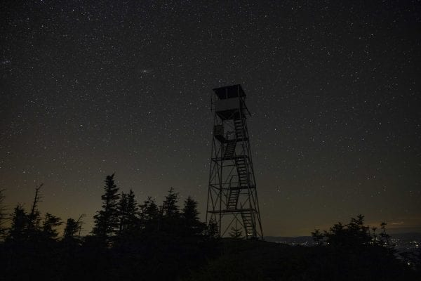 The Hurricane Mountain fire tower after dark under the stars. Photo by Mike Lynch