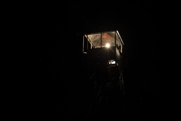 The fire tower cab was lit by a lantern Saturday night. Photo by Mike Lynch