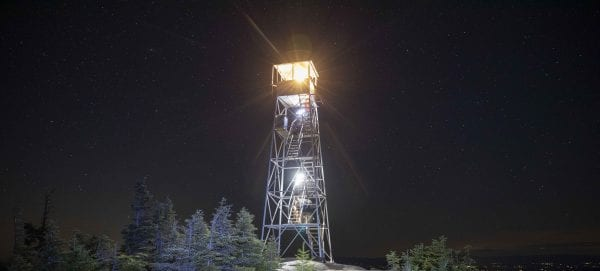 The fire tower cab was lit by a lantern. Hikers with headlamps can be seen climbing the stairs. Photo by Mike Lynch