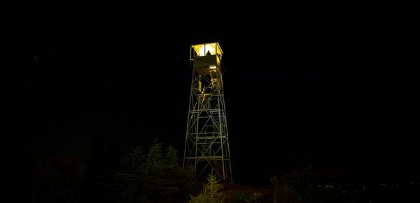 The Hurricane Mountain fire tower cab was lit by a lantern Saturday, August 31. The lighting was a statewide event to raise awareness of fire towers.  Photo by Mike Lynch