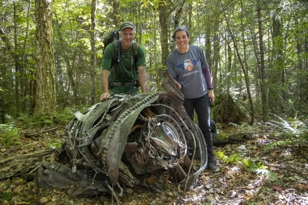 Adirondack 46ers Trail Master Sam Eddy and Explorer Publisher Tracy Ormsbee stand next to old plane wreckage they visited near Mud Pond in the Five Ponds Wilderness. Photo by Mike Lynch