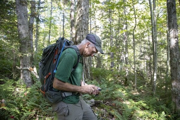 Adirondack 46ers Trail Master Sam Eddy checks his GPS during a bushwhack in the Five Ponds Wilderness. Photo by Mike Lynch