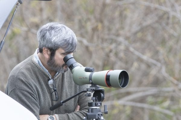 Explorer editor Brandon Loomis looks at the snow geese through a spotting scope. Photo by Mike Lynch