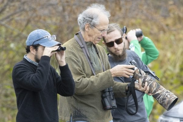 Explorer writer Ry Rivard looks through binoculars at the geese, as Larry Master and Explorer intern Ben Westcott look at images of the birds. Photo by Mike Lynch