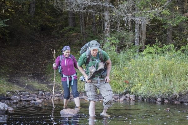 Sam Eddy and Tracy Ormsbee cross the Middle Branch of the Oswegatchie River in the Five Ponds Wilderness. Photo by Mike Lynch