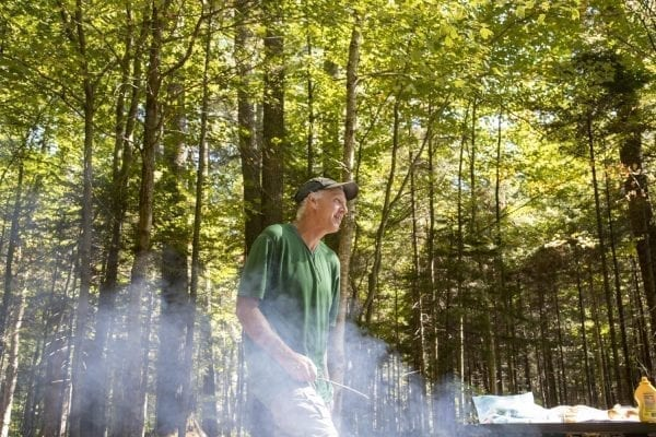 Sam Eddy cooks up some hot dogs at the Sand Lake lean-to. Photo by Mike Lynch