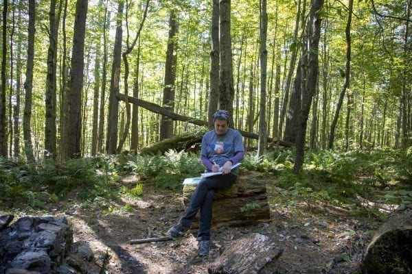 Explorer Publisher Tracy Ormsbee writes in the Wolf Pond lean-to journal. Photo by Mike Lynch