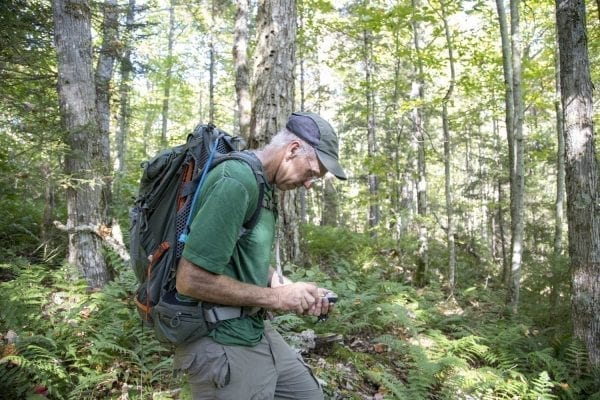 Sam Eddy looks at his GPS in the Five Ponds Wilderness. Photo by Mike Lynch