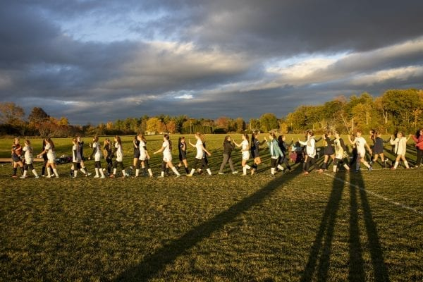 The Elizabethtown-Lewis-Westport high school girls soccer team (in black uniforms) congrats Keene players after a fall game in Westport. The school is an example of how districts are merging in rural areas. Photo by Mike Lynch