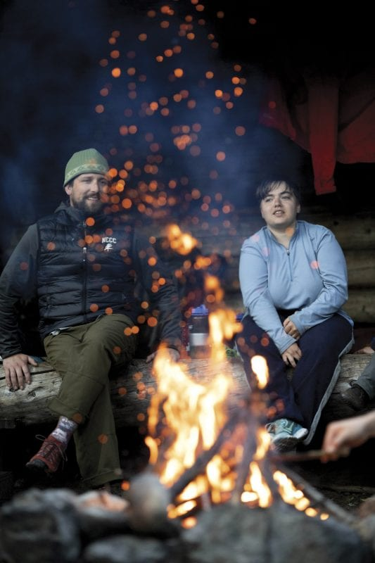 North Country Community College students take a monthlong wilderness trip every fall. Here wilderness recreation director Jimmy Cunningham and student Kim Hurst enjoy a fire by a Raquette River lean-to. Photo by Mike Lynch