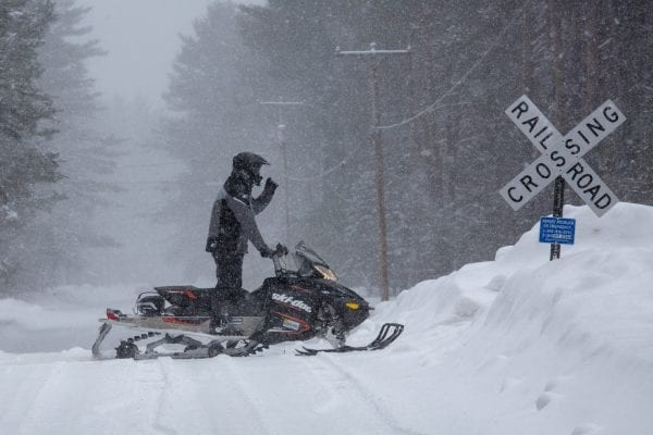 A snowmobiler stops on the much debated railroad line in Lake Clear in February 2019. Advocates of a rail trail have said the corridor would make a great biking and snowmobile trail with the tracks gone. Photo by Mike Lynch