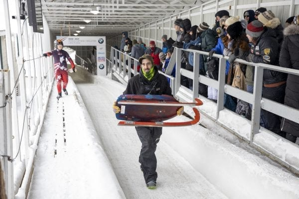 A track worker carries a sled off the track during a luge competition at Mount Van Hoevenberg in late February. Photo by Mike Lynch