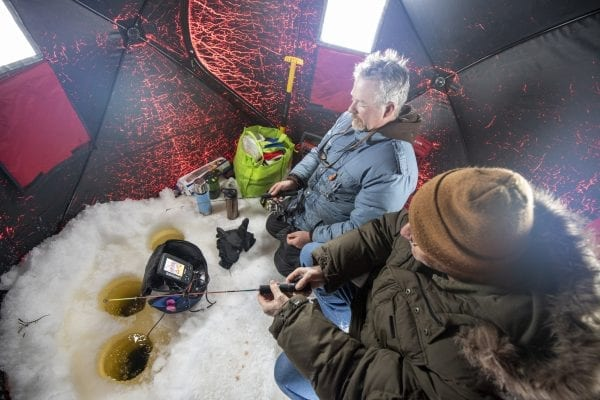 Guide Matt Burnett, left, and Explorer writer Tim Rowland fish in an ice shanty. Photo by Mike Lynch
