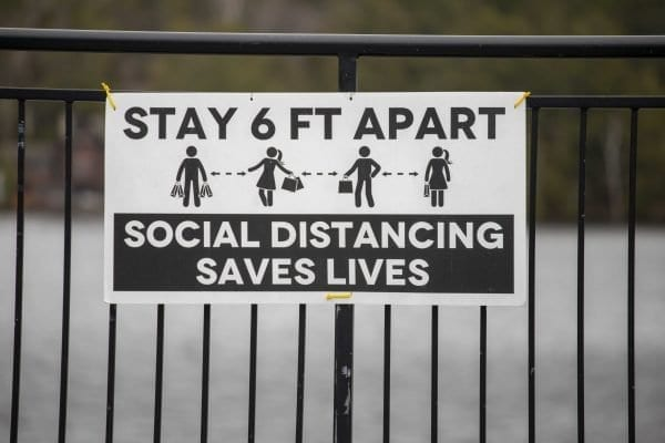 A sign in downtown Lake Placid encourages people to comply with social distancing guidelines. Photo by Mike Lynch