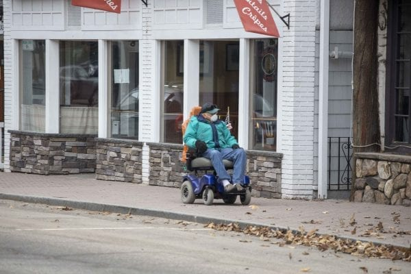 A man makes his way down Main Street in Lake Placid in late April. Photo by Mike Lynch
