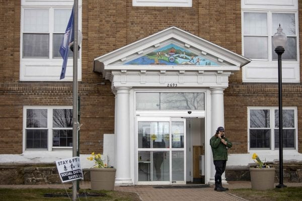 A man stands outside the North Elba Town Hall, where people can get free hand sanitizer in the front entrance room. Photo by Mike Lynch