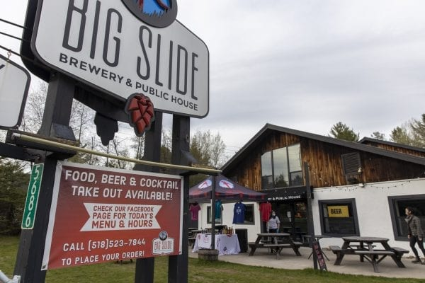 A customer picks up her order at Big Slide Brewery in Lake Placid in May. Photo by Mike Lynch
