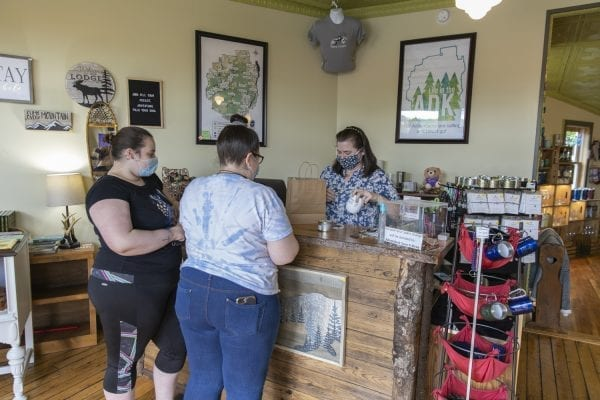 Michelle Bartlett, owner of Life in the ADK in Old Forge, helps customers in late May. Photo by Mike Lynch