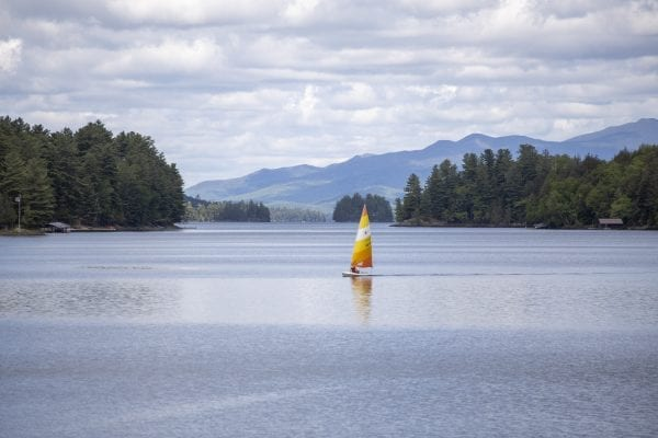 A man sails on a quiet Long Lake in late May. Photo by Mike Lynch