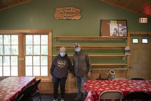 Judy and Ed Fuhr stand below a plaque honoring them inside a lodge at Higley Flow State Park. Photo by Mike Lynch