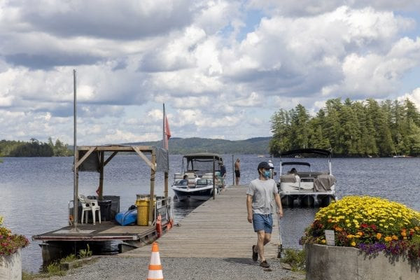 "This photo gallery shows a sleepy but scenic Raquette Lake on a Friday afternoon. The quiet scene is a result of a slowdown in tourism due to the pandemic. Most years Friday afternoons in July in this tiny hamlet are much busier, with boats waiting for space on the bustling dock as vessels and visitors come and go. This gallery is part of ""Snapshot,"" a multimedia series that captures a scene through photo galleries and videos. Photo by Mike Lynch"