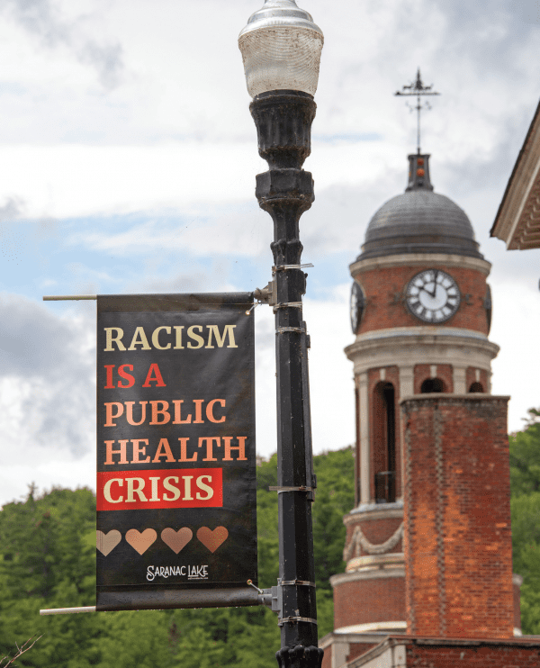 Anti-racism signs were placed in downtown Saranac Lake this summer. Photo by Mike Lynch