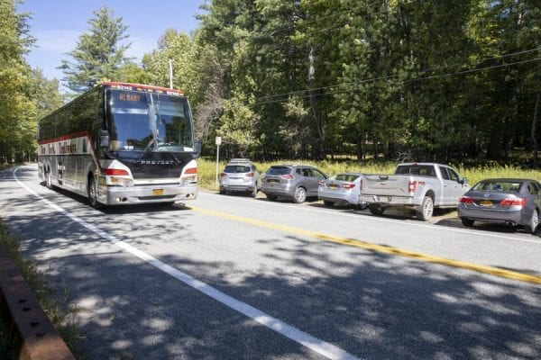 A bus drives down Route 73 by the Giant Mountain trailhead. Photo by Mike Lynch