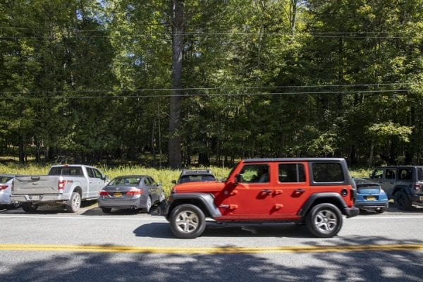 A jeep drives past vehicles that are parked illegally along Route 73 next to the Giant Mountain trailhead in St. Huberts. The vehicles are also parked perpendicular to the road. Photo by Mike Lynch