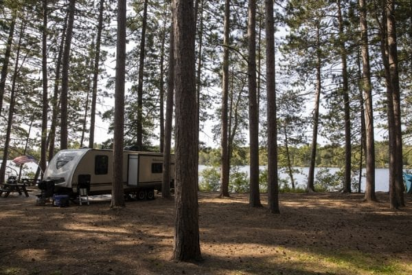 A trailer among the pines at the Fish Creek Pond Campground. Photo by Mike Lynch
