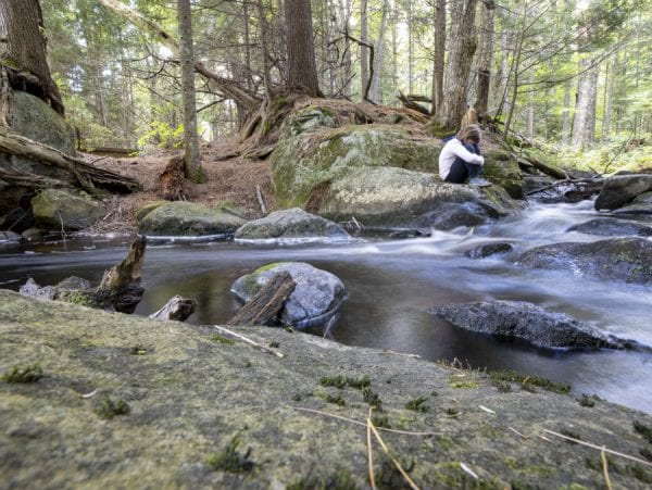 Sophia Kite relaxes by a stream. Photo by Mike Lynch