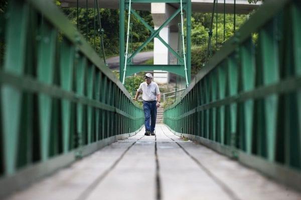 Don Lee, 75, walks the Saranac River Pedestrian Bridge in Plattsburgh.  Photo by Benjamin Chambers