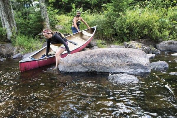 Cat Boland, 33, and Cooper Lambla, 32, both from North Carolina, prepare to canoe on the Saranac River near Frankin Falls Road. Photo by Benjamin Chambers