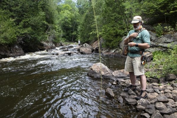 Jeff Snyder, of Sandy Hook, Connecticut, has fished in the Saranac for 35 years. During an annual family trip this summer he helped his niece, Nicole Whelan, and her husband Matt catch and release fall fish and small mouth bass near Franklin Falls. Photo by Benjamin Chambers
