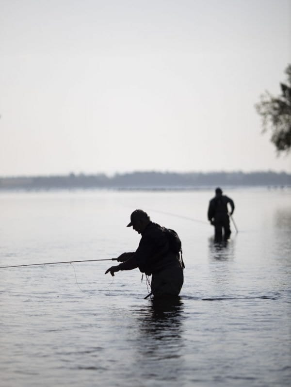 A silhouette of anglers fishing near the mouth of the Saranac River. Lake Champlain is in the background. Photo by Mike Lynch