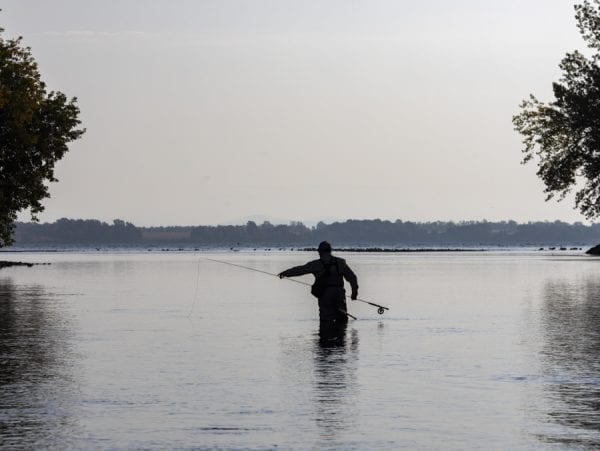 An angler adjusts his gear at the mouth of the Saranac River. Photo by Mike Lynch
