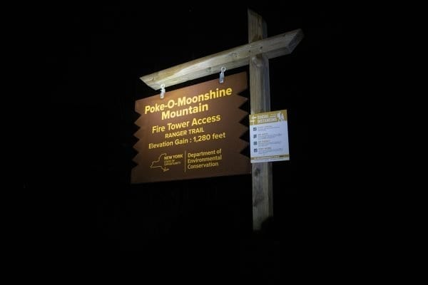 The Poke-O-Moonshine Ranger trail sign lit up by a headlamp. Photo by Mike Lynch