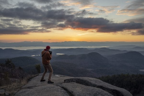 Shane Kenyon walks on the summit of Poke-O-Moonshine Mountain in the eastern Adirondacks at sunrise. photo by Mike Lynch