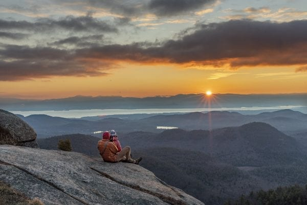 Shane Kenyon and Erika Guli enjoy a sunrise from Poke-O-Moonshine Mountain in the eastern Adirondacks. photo by Mike Lynch