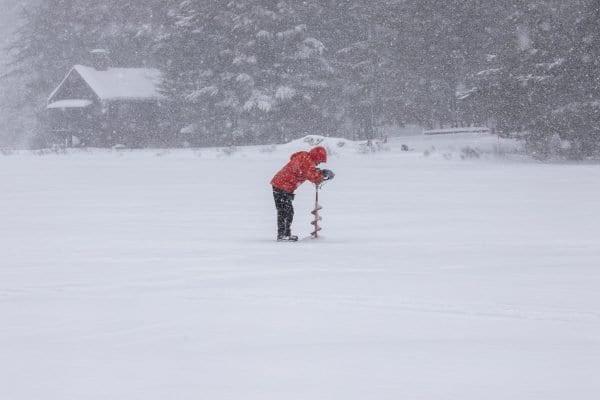 Glenn Goldman drills a hole into the ice on Osgood Pond. Photo by Mike Lynch