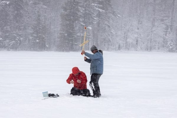 Glenn Goldman, left, checks the line for fish on Osgood Pond on a frigid February day as guide Matt Burnett assists him. Photo by Mike Lynch