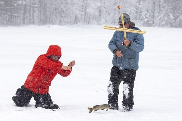 Glenn Goldman, left, pulls a northern pike from Osgood Pond on a frigid February day as guide Matt Burnett looks on. Photo by Mike Lynch