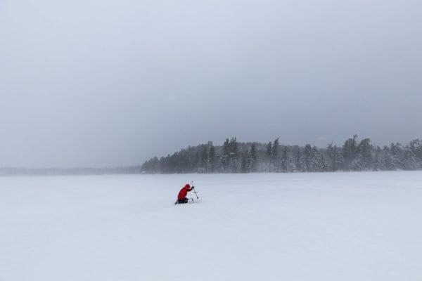 Glenn Goldman checks a tip up on Osgood Pond. Photo by Mike Lynch