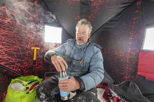 Guide Matt Burnett gets a hot drink from his thermos inside his ice fishing shanty. Photo by Mike Lynch
