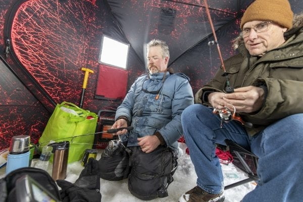 Matt Burnett and Tim Rowland jig inside the ice fishing shanty on Osgood Pond. Photo by Mike Lynch
