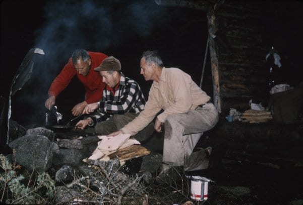 Clarence Petty helps a legislative fact-finding team make dinner over a campfire in 1961.