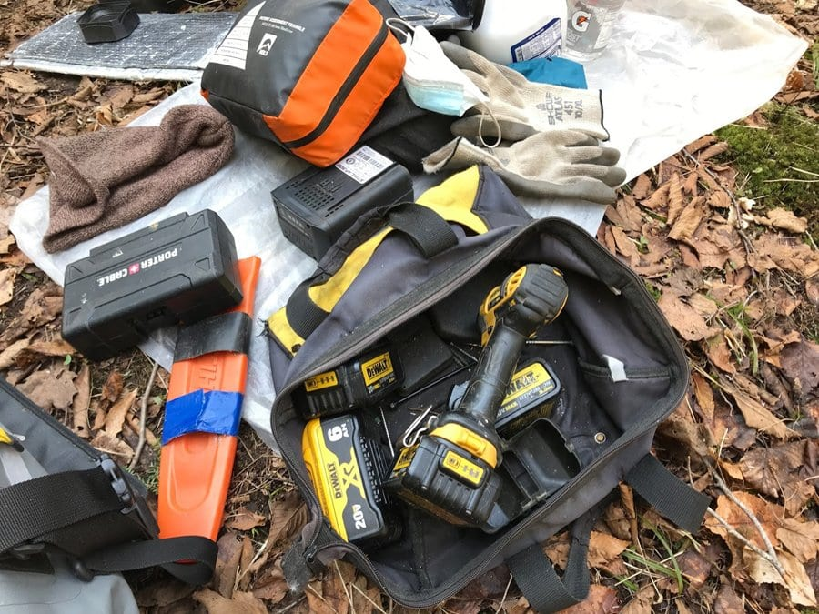 Tools and a surgical mask rest on the ground at the Kiwassa Lake lean-to site.