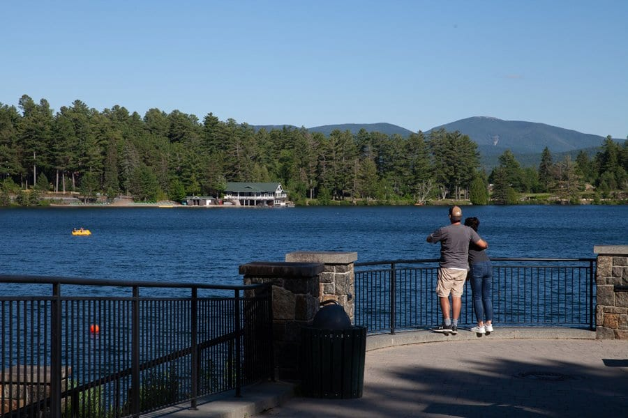 A couple looks across Lake Mirror to the Adirondack Mountains from Lake Placid's waterfront.