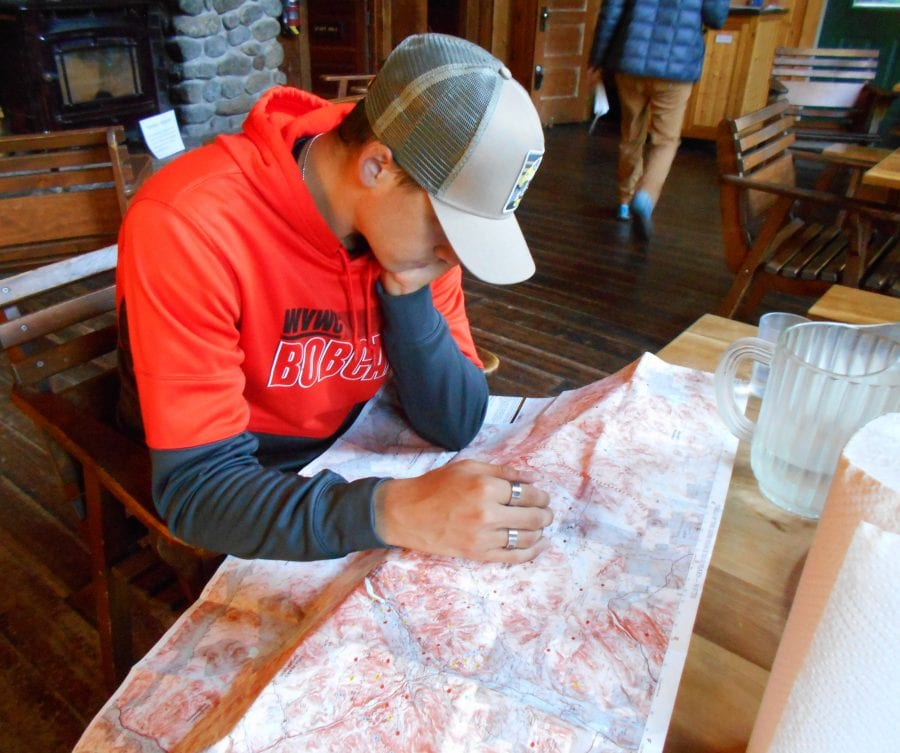 Nathan looking over map for Mt. Marcy hike at Johns Brook Lodge.